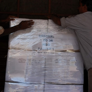 Workers shrink wrapping a pallet
